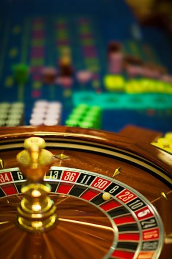 closeup of a wooden roulette wheel, with betting chips behind